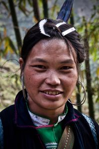 Young H'mong girl wearing her hair pulled up on her head and clipped several times using slides and a hair comb.