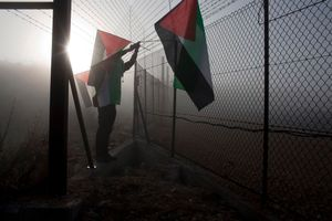 Palestinian activists hang the Palestinian flag during a direct action against the Separation Wall and the occupation, West Bank, 2013.