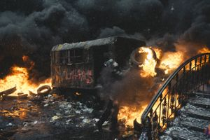 A protester carries a burning car ramp closer to the riot police cordon in the center of Kiev, Jan. 22, 2014