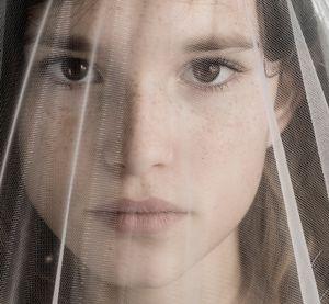 Behind a veil.