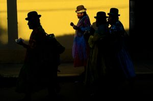 Cholitas walk on the street at sunset after an exhibition fight on the rich part of La Paz. The wrestling cholitas fight every Sunday on the 12th October Sports Complex in El Alto, at times they do exhibition fights in other parts of La Paz to promote the sport.