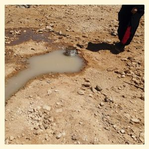 A small boy stands near a stream of waste water, Za'atari