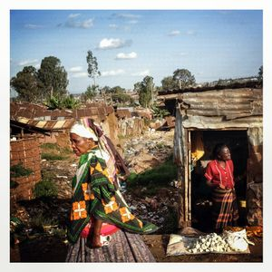 An elderly woman passes the main valley of Kibera which is filled with shacks covered with corrugated iron. The Kibera slum is the largest slum in Nairobi with around half a million inhabitants.