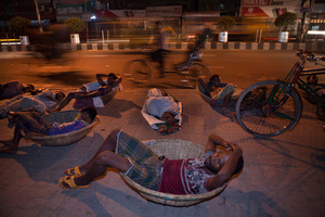 Daily-wage workers sleep on the roadside by the Kawran Bazar in Dhaka. A large number of homeless people in Dhaka have lost their homes and properties through floods, river erosion and other natural calamities, and come to the city in the hope of a better future.
