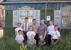 Family of ten in Petrovka in front of their old house which will be demolished soon, Petrovka, Omsk Oblast, Russia, 2014