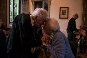 Mrs Carla Magni, receives a warm hug from Mrs Rosa Silva, 92 years old, during the celebration of Carla's 100 years birthday.