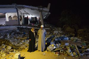 Wasfai Hamdan Al-Najar, 56, and his wife Fawzaya Ebrahem, 51, pose in front of their home in Khan Yunis destroyed by Israeli airstrike during the summer's 50-day war. They finally, two days before, got the space to sleep. Yet it is only at night. They stay at this dangerously destroyed house with their children in day time.
