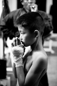 A boy is praying before the fight. His trainer smokes a cigarette at the background. © Sandra Hoyn
