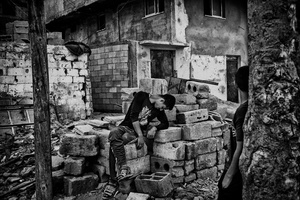A young man rests near his destroyed house in the evening after a day of work