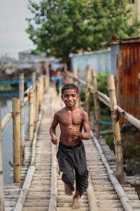 Boy running across a bridge