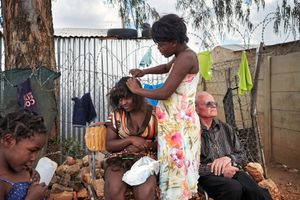 Father Hermann rests while some girls are doing their hair. It took a few years until the women started to trust the priest. But now many say that he is like a real father to them. He became part of the family, part of the people in the township.