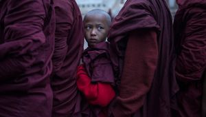 Monk kid standing in line for charity in Ananada pagoda