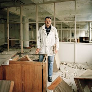 Milenko Krenaic', chief engineer at the Borovo shoe factory, stands at his old desk. © Colin Dutton