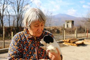 Zdravka, the mother of the owner of a sawmill, with one of the six puppies born by the factory dog. Sandanski, Bulgaria.