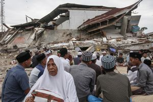Survivors perform a special prayer for the victims were killed in an 6.5 earthquake outside a collapsed building in Pidie Jaya, Aceh province, on December 9, 2016.