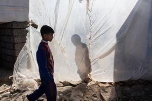 22/01/2015 -- Kirkuk, Iraq -- An Iraqi boy with the Barcelona football club's t-shirt walks among tents and plastic sheets in the Laylan IDP cam in south of Kirkuk.