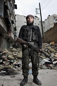 An FSA fighter stands with his rifle on a street damaged by fighting in the Shaar district of Aleppo, February 7, 2013.  © Nish Nalbandian