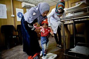 A nurse for Médecins du Monde helps a mother weigh her child. © Tom Verbruggen