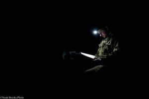 Soldier Reads Bible in Dark Dugout