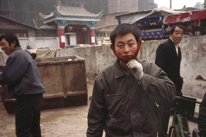 Workers return the gaze of the Lowai (stranger) photographer, the red wool ear muffs are traditionally worn by manual labourers.  Xi'an, China. 22 December 2006.