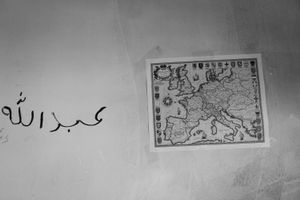 """A map of Europe and the Name """"Abdullah"""" in Arabic script on a wall inside the barracks."""