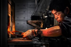 Bladesmith is watching the steel color if its ready for forging.