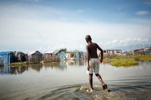 A boy walking through the flooded landscape at Rapatriès.