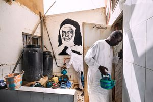 On June 17 2018, a follower of the Layene Brotherhood enters the washing room at the house in Ngor in Dakar, where allegedly holy water springs from the ground. Another follower of the brotherhood fills pots with the water from a copper pipe. On the wall is a painting of the face of Seydina Issa Rouhou Laye (1909-1949), who was the son of Limamou Laye (1843–1909), the founder of the brotherhood.