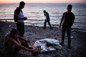 September 2015, Lebsos, Greece. These refugees just arrived in a packed little boat full of refugees. The motor of their boat broke down, letting them turn over the wild sea for hours. They are exhausted and chilled.