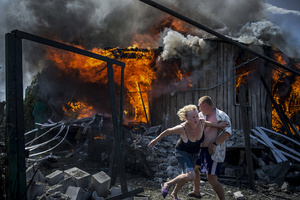 Civilians escape from a fire at a house destroyed by the  air attack