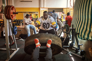 The Wrestler Forza trains with his colleague Diene Kaire Kaire with a truck tyre, in the Olympique club on April 3, 2015. Only the stars of the Senegalese wrestling scene can afford to train at this posh club in the district of Mermez in Dakar.