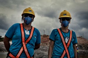 Two workers of the building consortium inside the working area. At its peak, the construction will give job to 40.000 people, but will dismiss everyone as soon as it will be completed by 2019. It is not clear what will happen to these people and the city when the working opportunities will cease.   © Dario Bosio/Parallelozero