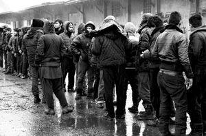 in fila, sotto la pioggia, aspettando un l'unico pasto caldo della giornata distribuito dai volontari