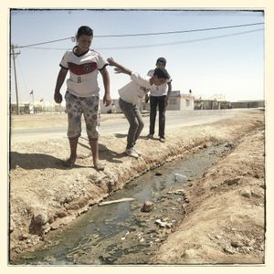 (left to right) Omar*, Salem* and Ali* prepare to jump over a waste water stream.