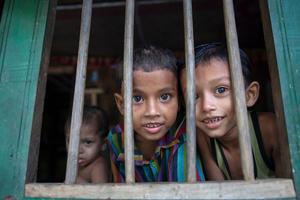 Children look through the window at Morrelganj, Bagerhat, Bangladesh