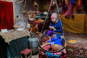 A Uighur woman takes care of her child at home in old Kashgar, Xinjiang Uighur Autonomous Region, China.