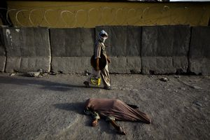 A handicapped child covered in a blanket lies on the road near the center of Kabul. © Michael Christopher Brown