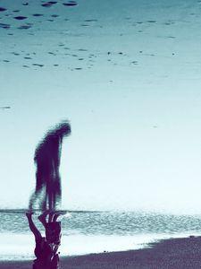 À travers le reflet de l'eau, une silhouette se dessine