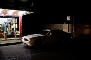 Two youngsters in a Ford Mustang wait for their friend, buying licquor in a nightshop in Ankawa, the Christian part of Erbil. © Tom Verbruggen