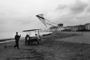 A couple selling their goods at the beach, even during winter, when almost no one visits. Durres, Albania © Enri Canaj