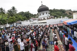 Survivors perform Friday mass prayer outside a collapsed Jami Quba Mosque following the earthquake in Pidie Jaya, Aceh province, on December 9, 2016.