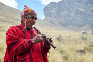 """A farmer (""""campesino"""") takes a break  from harvesting potatoes to play music in traditional dress. Huamanachoque, Peru"""