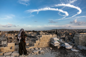 A YPJ fighter looks over the wreckage left by fighting on a street in Kobane, Syria, on 31 March 2015