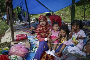 A mother with her daughters take rest in a makeshift tent following the earthquake in Pidie Jaya, Aceh province, on December 10, 2016.