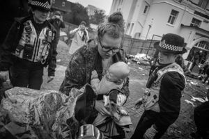 A mother  is protected by the Police as things start to get out of hand