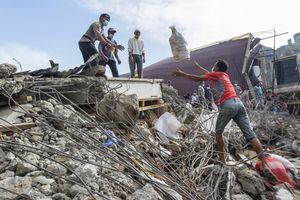 Volunteer throw an items that survived to Indonesian policeman during search and rescue operation at the collapsed building in Pidie Jaya, Aceh province, on December 10, 2016.