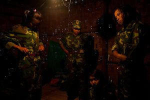 Women change into their uniforms in the room that 10 of them shared during their military training at the 3rd Brigade army base in Mai Ja Yang, Kachin State, Myanmar, May 30, 2013. While some of the women had joined out of their own interest in serving with the KIA, an equal number of women had been forcibly recruited.                     © Adriane Ohanesian