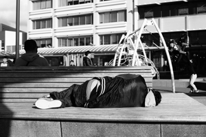 Man sleeping rough at a playground in Porirua (New Zealand), a suburb of contrasting low- and high-income households