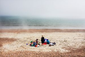 """It is mid-afternoon. The weather is sunny. Travelling in the south of England, I am walking on Hayling beach. A sudden fog comes down on the beach changing dramatically its atmosphere. A feeling of strangeness. I take a photograph of this family as I walk past. A few minutes later, the fog disappears, as fast as it came."""