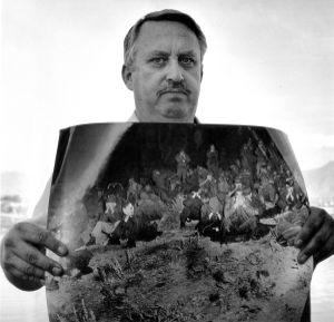 """Atomic Veteran Robert Carter holds a prize possession, a photo of himself with his Air Force squad a few miles from Ground Zero right before Shot Hood was detonated on July 5, 1957, at 74 kilotons the biggest atmospheric atomic bomb ever tested in Nevada. """"I was happy, full of life before I saw that bomb, but then I understood evil and was never the same."""" Taylorsville, Utah, 1988"""